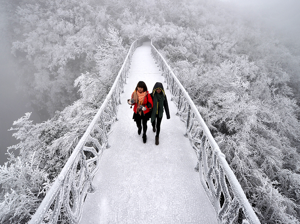 Tourists walk on a bridge covered by frosty fog on the Tianmen Mountain resort in Zhangjiajie
