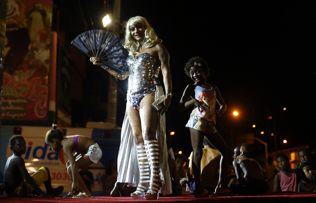 A girl poses next to a reveller at the entrance of the Glam Gay pre-carnival Ball, in Mangueira samba school in Rio de Janeiro