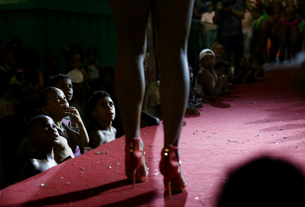 Residents of Mangueira slum watch as a participant attends a beauty contest for transvestites and transsexuals at the entrance of the Glam Gay pre-carnival Ball, in Mangueira samba school in Rio de Janeiro