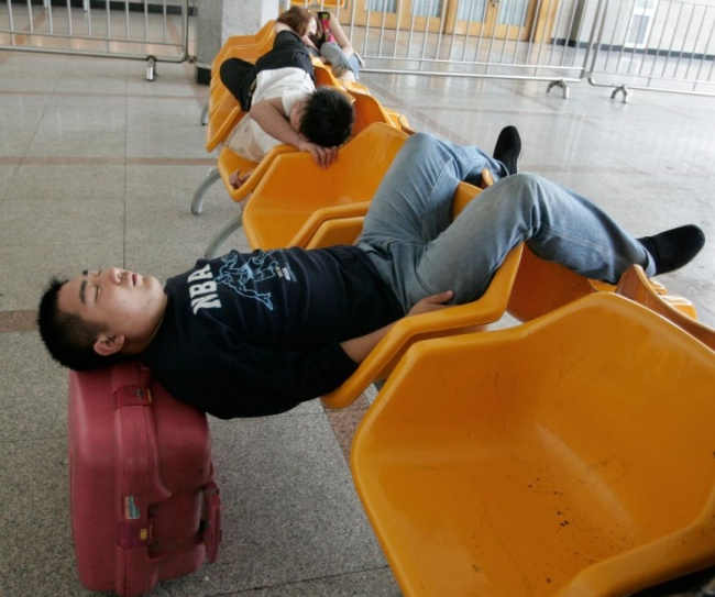 14173360-R3L8T8D-650-80348-a-traveller-sleeps-while-waiting-for-his-train-at-the-beijing-railway-