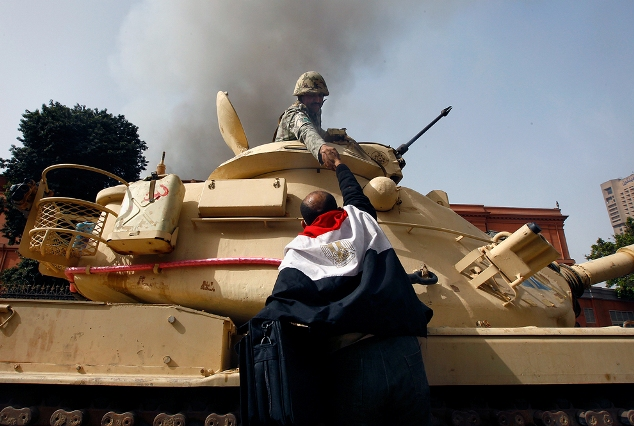 A protester draped in an Egyptian flag climbs atop an army tank to shake hands with a soldier in Cairo January 29, 2011. Egyptian President Hosni Mubarak refused on Saturday to bow to demands that he resign after ordering troops and tanks into cities in an attempt to quell an explosion of street protests against his 30-year rule. REUTERS/Yannis Behrakis (EGYPT - Tags: POLITICS CIVIL UNREST IMAGES OF THE DAY)